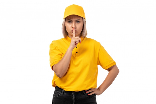 A front view female courier in yellow shirt yellow cap and black jeans posing showing silence sign on white