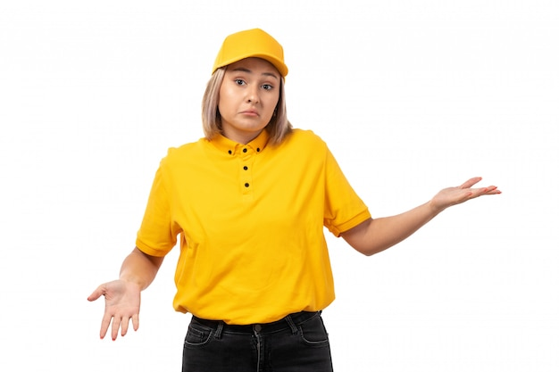 A front view female courier in yellow shirt yellow cap and black jeans posing on white
