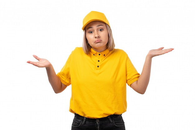 A front view female courier in yellow shirt yellow cap and black jeans posing with do not know expression on white