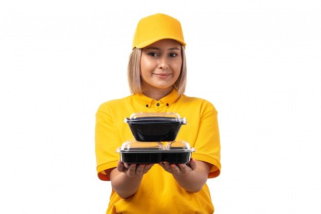 A front view female courier in yellow shirt yellow cap black jeans smiling holding bowls with food on white