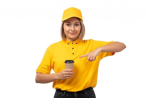A front view female courier in yellow shirt yellow cap and black jeans smiling holding coffee cup on white