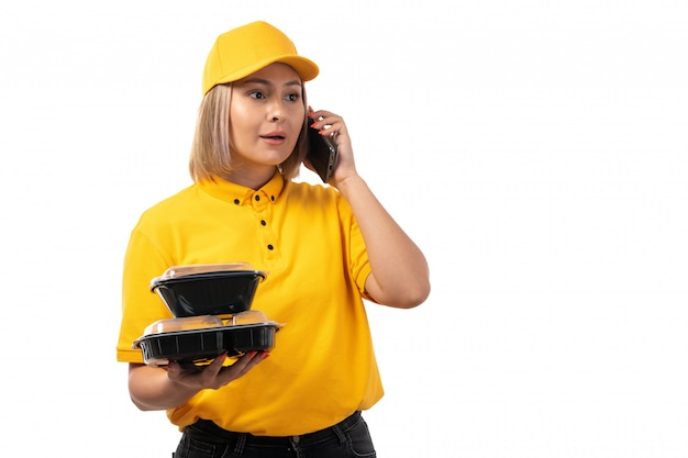 A front view female courier in yellow shirt yellow cap holding bowls with food talking on phone on white