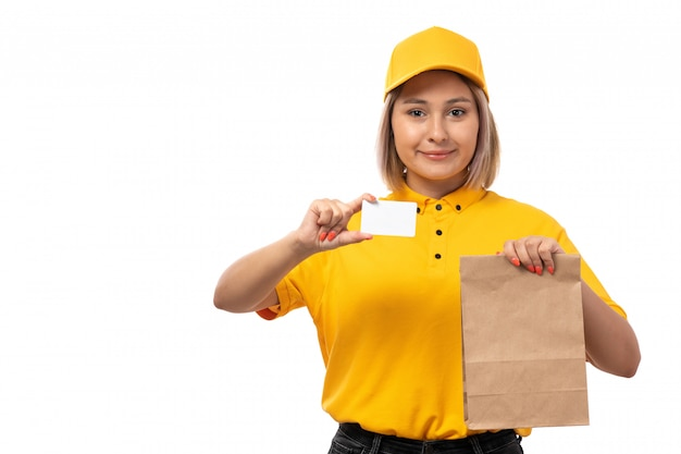 A front view female courier in yellow shirt and yellow cap holding bowls with food and white card on white