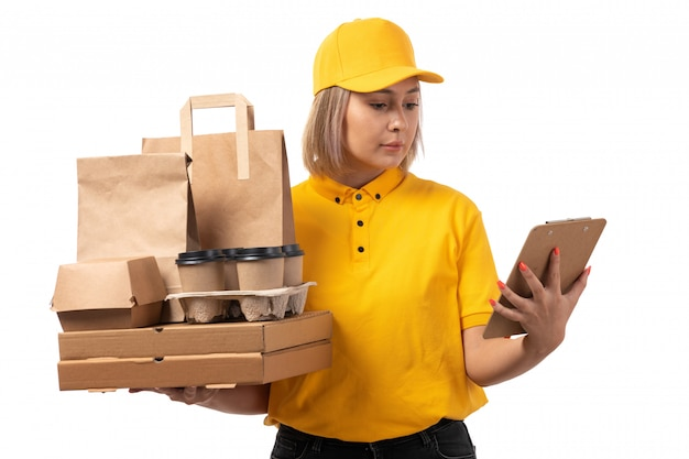 A front view female courier in yellow shirt yellow cap holding boxes coffee paper on white