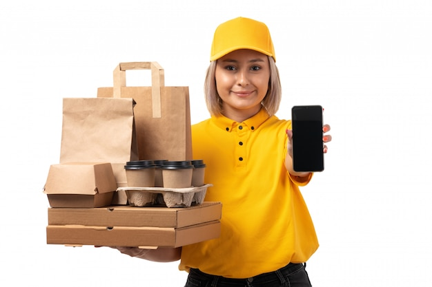A front view female courier in yellow shirt yellow cap holding pizza boxes phone coffee smiling on white