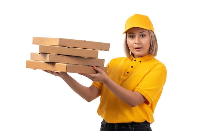 A front view female courier in yellow shirt yellow cap holding pizza boxes on white