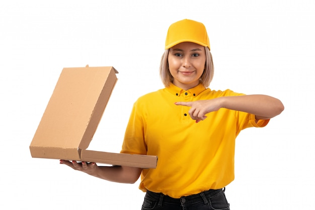 A front view female courier in yellow shirt yellow cap smiling holding box on white