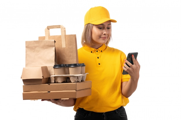 A front view female courier in yellow shirt yellow cap smiling holding smartphone and boxes on white