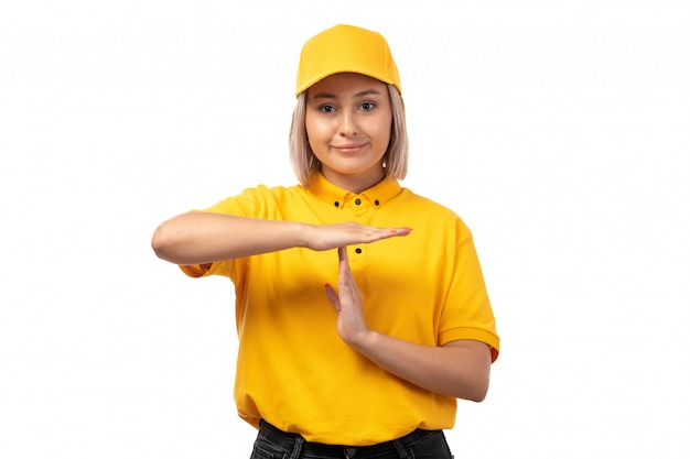 A front view female courier in yellow shirt yellow cap smiling showing t word on white