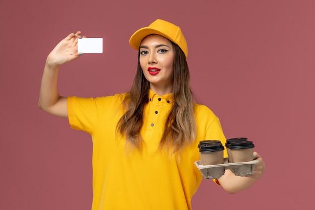 Vista frontale del corriere femminile in uniforme gialla e cappuccio che tiene le tazze e la carta di caffè marroni sulla parete rosa