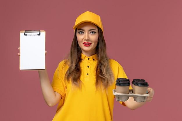 Vista frontale del corriere femminile in uniforme gialla e cappuccio che tiene tazze di caffè marroni e blocco note sulla parete rosa