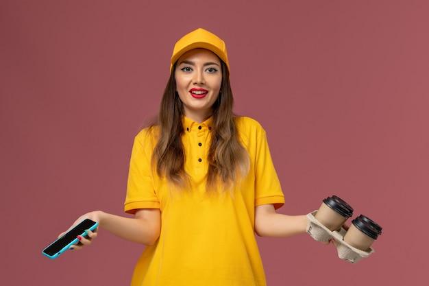 Vista frontale del corriere femminile in uniforme gialla e cappuccio che tiene tazze di caffè marroni e parla al telefono sulla parete rosa