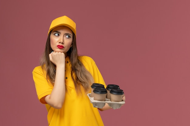 Vista frontale del corriere femminile in uniforme gialla e cappuccio che tiene tazze di caffè marroni di consegna e che pensa profondamente sul muro rosa