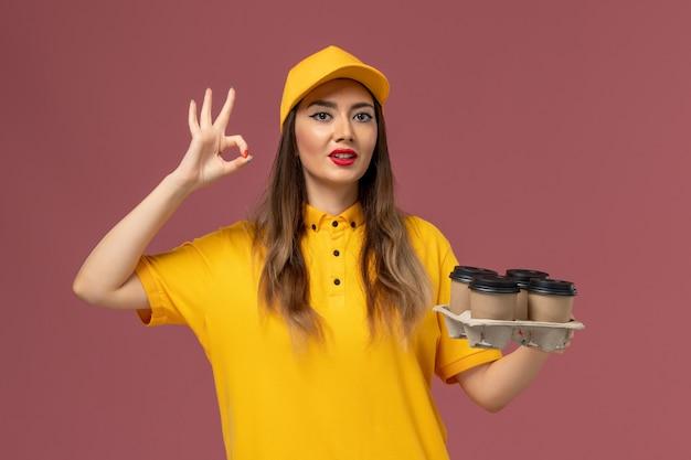 Vista frontale del corriere femminile in uniforme gialla e cappuccio che tiene le tazze di caffè marroni di consegna sulla parete rosa