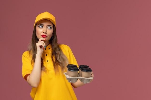 Vista frontale del corriere femminile in uniforme gialla e cappuccio che tiene le tazze di caffè marrone di consegna e pensa sulla parete rosa