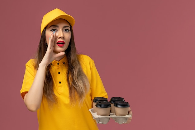 Front view of female courier in yellow uniform and cap holding brown delivery coffee cups whispering on pink wall