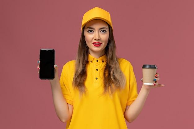 Vista frontale del corriere femminile in uniforme gialla e cappuccio che tiene la tazza di caffè e il telefono di consegna sulla parete rosa
