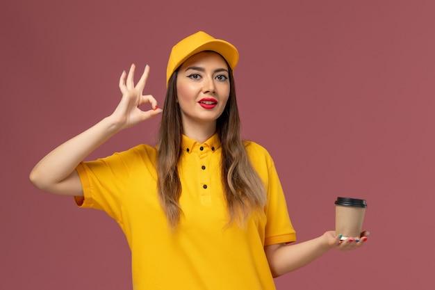 Vista frontale del corriere femminile in uniforme gialla e cappuccio che tiene la tazza di caffè di consegna sulla parete rosa