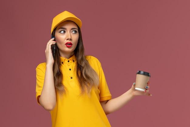 Vista frontale del corriere femminile in uniforme gialla e cappuccio che tiene la tazza di caffè di consegna e parlando al telefono sulla parete rosa