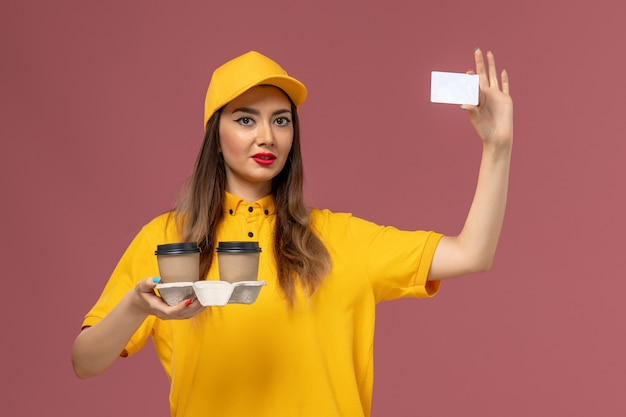 Front view of female courier in yellow uniform and cap holding delivery coffee cups and card on pink wall