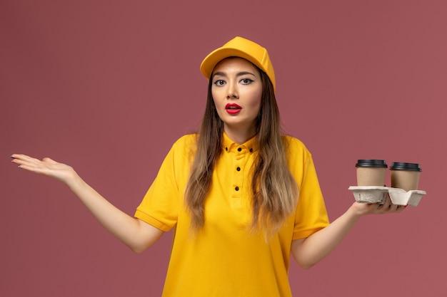 Vista frontale del corriere femminile in uniforme gialla e cappuccio che tiene le tazze di caffè di consegna sulla parete rosa