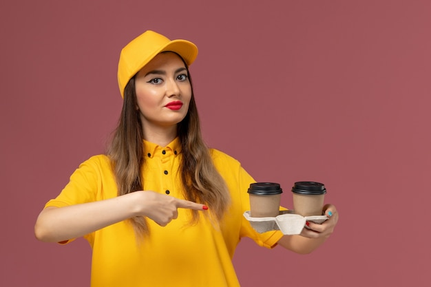 Front view of female courier in yellow uniform and cap holding delivery coffee cups on pink wall