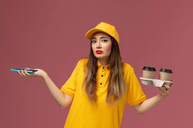 Front view of female courier in yellow uniform and cap holding delivery coffee cups and smartphone on pink desk