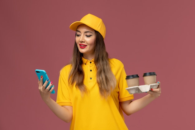 Front view of female courier in yellow uniform and cap holding delivery coffee cups and smartphone on pink wall