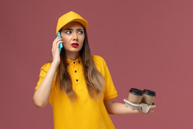 Vista frontale del corriere femminile in uniforme gialla e cappuccio che tiene le tazze di caffè di consegna e parla al telefono sulla parete rosa