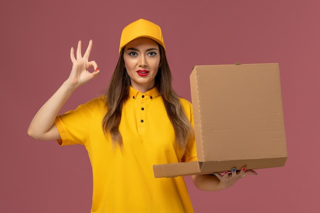 Front view of female courier in yellow uniform and cap holding empty food box on light pink wall