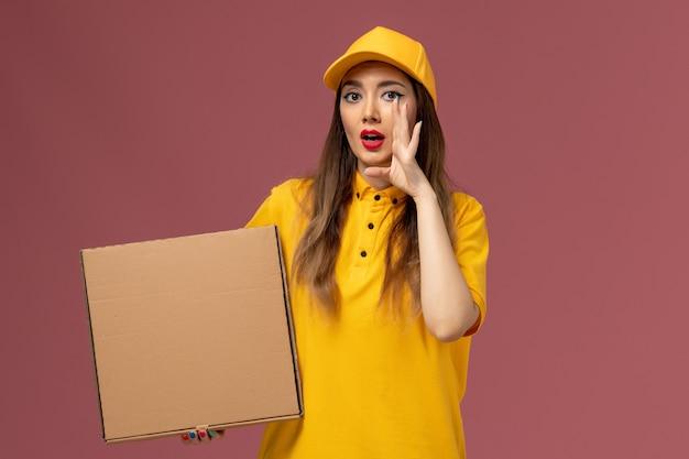 Vista frontale del corriere femminile in uniforme gialla e cappuccio che tiene la scatola del cibo e chiama sul muro rosa chiaro