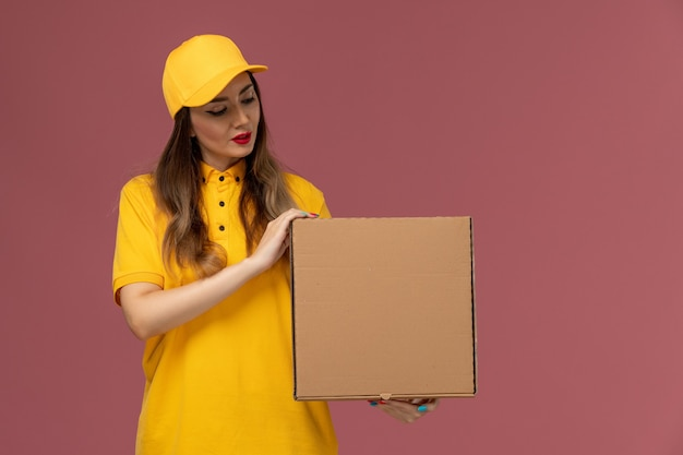 Front view of female courier in yellow uniform and cap holding food box on the light-pink wall
