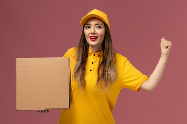 Vista frontale del corriere femminile in uniforme gialla e cappuccio che tiene la scatola di cibo sulla parete rosa chiaro