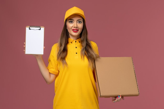 Vista frontale del corriere femminile in uniforme gialla e cappuccio che tiene scatola di cibo e blocco note sulla parete rosa chiaro
