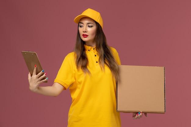 Vista frontale del corriere femminile in uniforme gialla e cappuccio che tiene la scatola di cibo e il blocco note sulla parete rosa