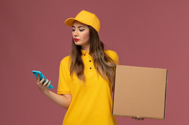 Front view of female courier in yellow uniform and cap holding food box and phone on light-pink wall