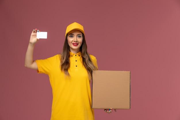 Vista frontale del corriere femminile in uniforme gialla e cappuccio che tiene scatola di cibo e carta di plastica sulla parete rosa chiaro