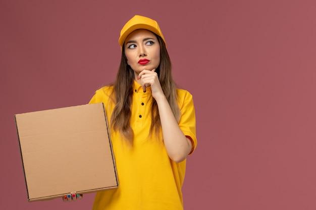 Vista frontale del corriere femminile in uniforme gialla e cappuccio che tiene il contenitore di cibo pensando sulla parete rosa chiaro