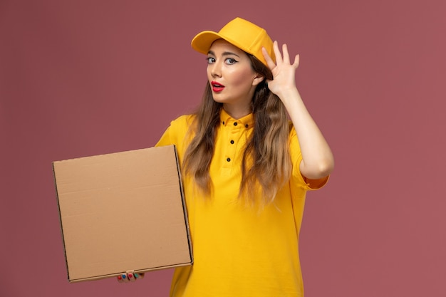 Front view of female courier in yellow uniform and cap holding food box trying to hear on the light-pink wall