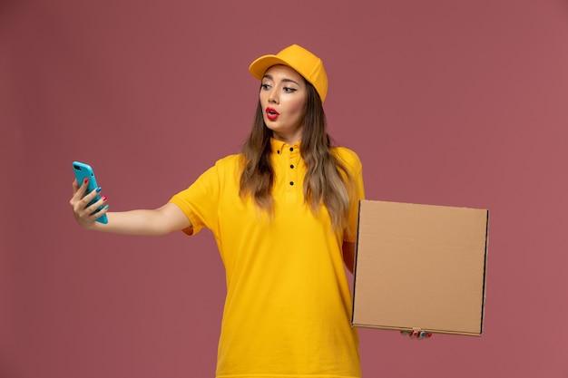 Vista frontale del corriere femminile in uniforme gialla e cappuccio che tiene scatola di cibo e telefono di lavoro sulla parete rosa chiaro
