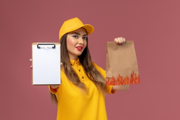 Front view of female courier in yellow uniform and cap holding food package and notepad on pink wall