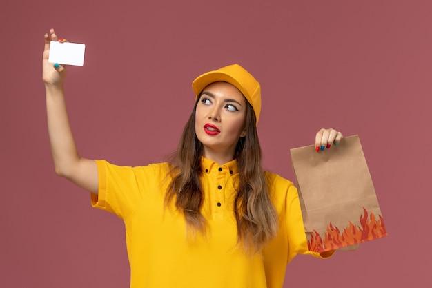 Vista frontale del corriere femminile in uniforme gialla e cappuccio che tiene il pacchetto di cibo e carta di plastica sulla parete rosa