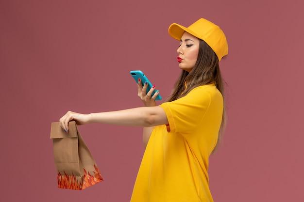 Vista frontale del corriere femminile in uniforme gialla e cappuccio che tiene il pacchetto alimentare e scattare una foto sul muro rosa