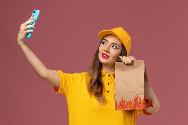 Vista frontale del corriere femminile in uniforme gialla e cappuccio che tiene il pacchetto di cibo e prendendo un selfie sul muro rosa
