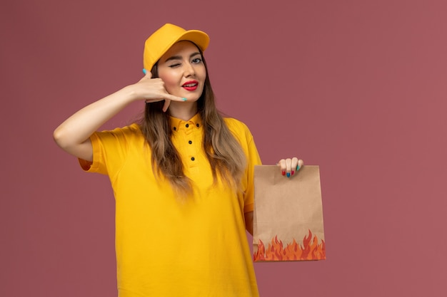 Front view of female courier in yellow uniform and cap holding food package winking on light-pink wall