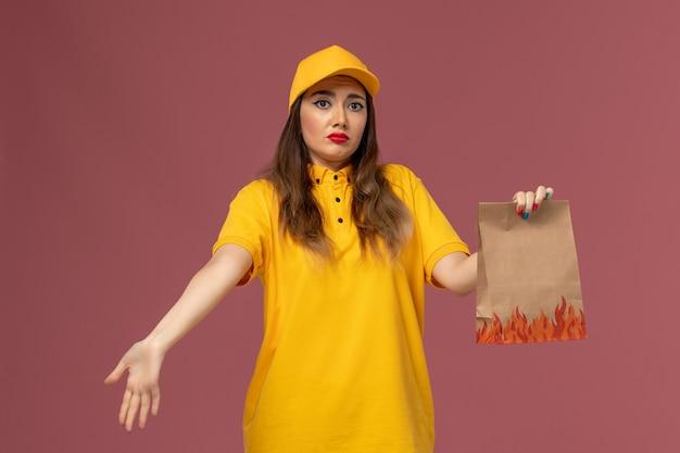 Vista frontale del corriere femminile in uniforme gialla e cappuccio che tiene il pacchetto alimentare con espressione ocnfused sulla parete rosa chiaro