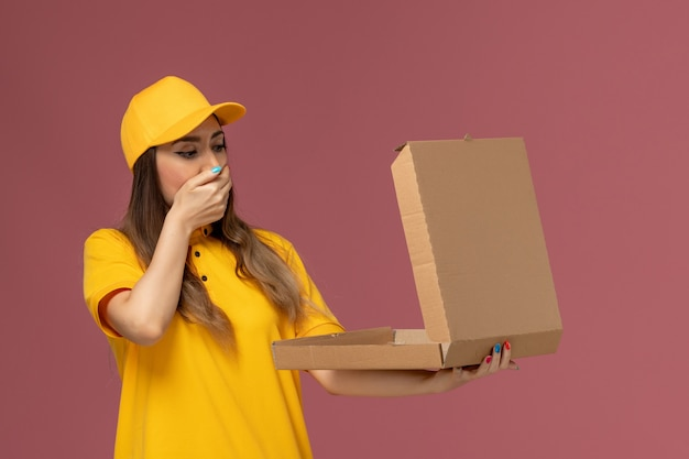 Front view of female courier in yellow uniform and cap holding open food box with shocked expression on pink wall