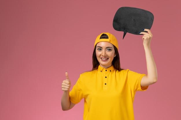Corriere femminile di vista frontale in uniforme gialla e mantello che tiene grande segno nero sulla consegna dell'uniforme del lavoratore del lavoro di servizio della parete rosa