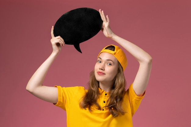 Corriere femminile di vista frontale in uniforme gialla e mantello che tiene segno nero sul lavoro dell'azienda dell'uniforme di consegna di servizio della parete rosa chiaro
