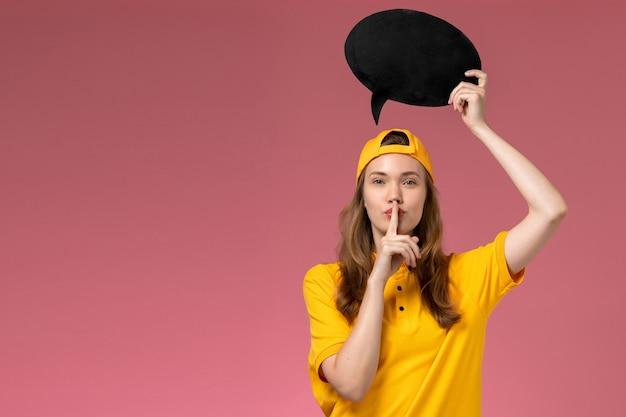 Corriere femminile di vista frontale in uniforme gialla e mantello che tiene segno nero sul lavoro di lavoro dell'uniforme di consegna di servizio dell'azienda della parete rosa